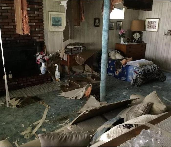 Cluttered room with fireplace and debris on floor