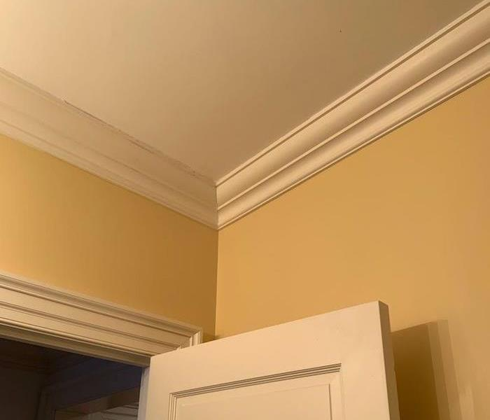 Ceiling and walls over a doorway with fresh paint