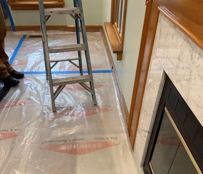 SERVPRO tech with ladder on plastic barriers in living room