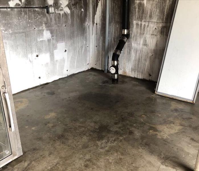 Basement with smoke damage on brick walls