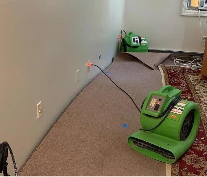 A room with the carpet lifted, with SERVPRO equipment 0n the carpet.