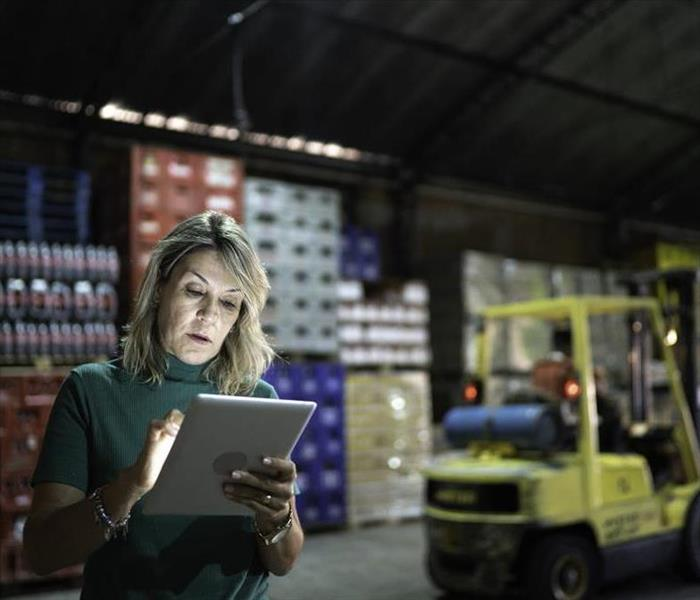 A female standing in a warehouse.