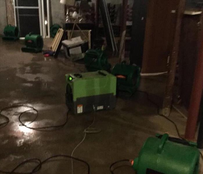 SERVPRO equipment in a basement that has water on the floor.