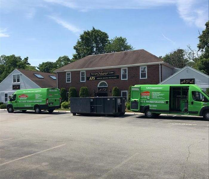 two SERVPRO vans at jobsite with doors open
